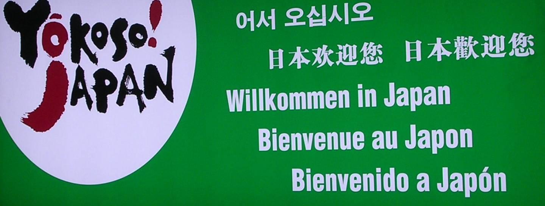 """Schild am Narita Flughafen, auf dem """"Willkommen in Japan"""" in verschiedenen Sprachen steht"""