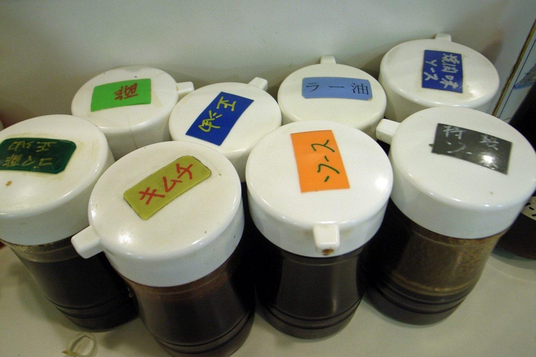 Beschriftete Saucenbehälter in einem japanischen Restaurant