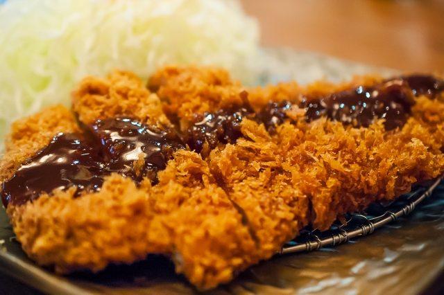 Tonkatsu mit Suace auf einem Teller serviert
