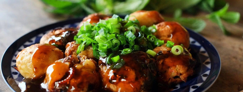 Takoyaki auf einem Teller mit Sauce