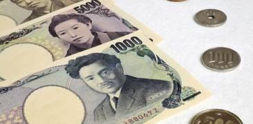 Yen-Scheine und -Münzen auf einem Tisch drapiert