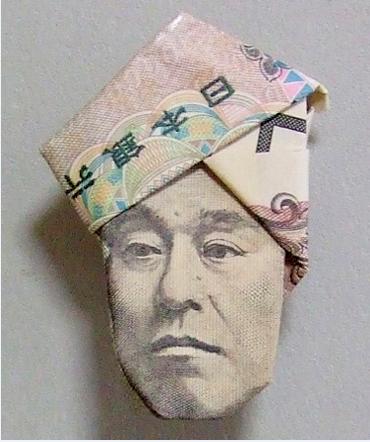 Ein zu einem Gesicht mit Hut gefalteter 10.000 Yen Schein