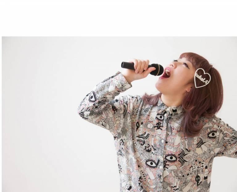 Beim Karaoke: Singende Frau mit Mikrofon