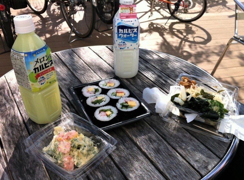 Sushi und Getränke aus einem Konbini auf einem Tisch angerichtet