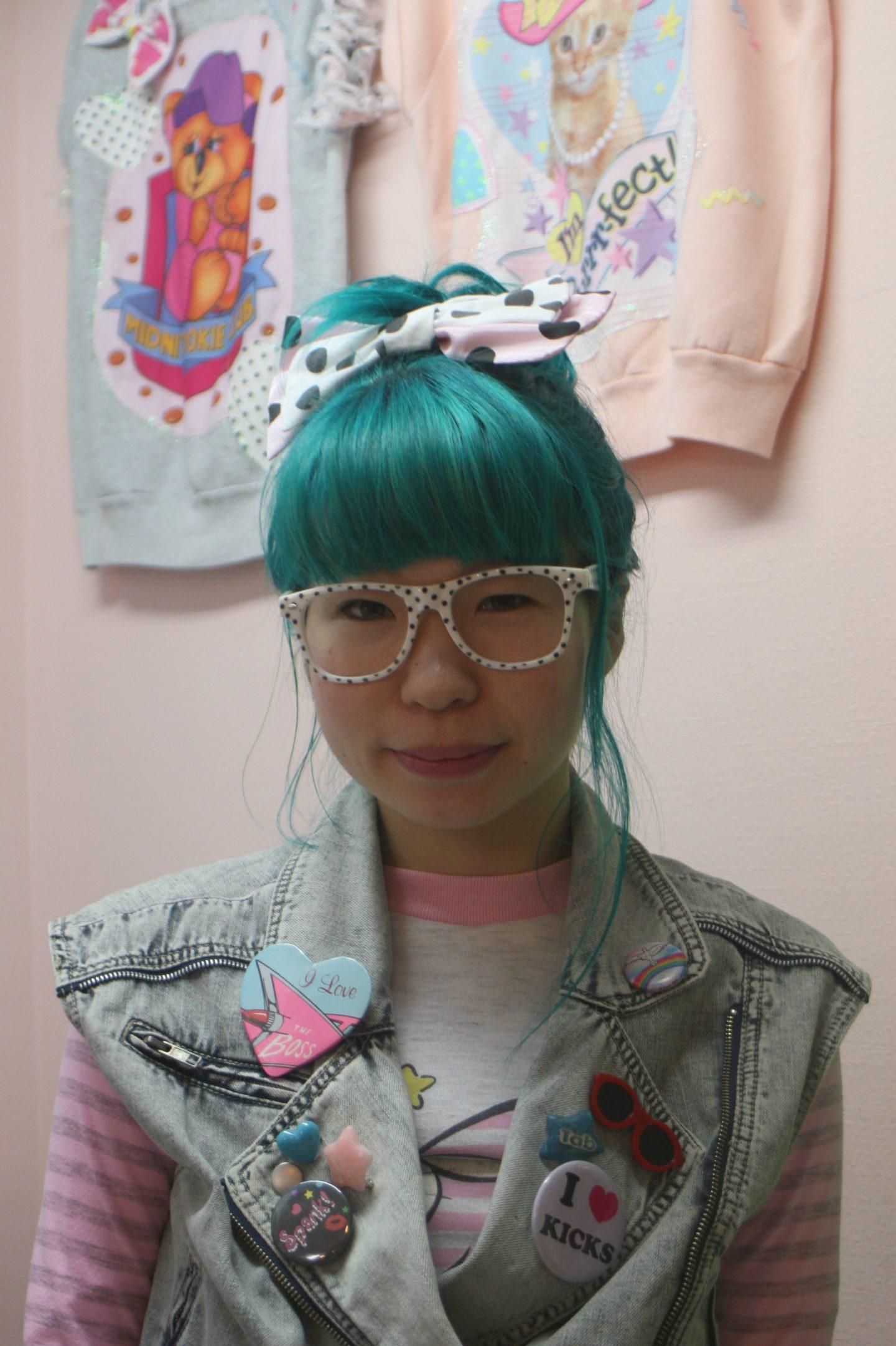 Japanerin mit Brille und grünen Haaren posiert für ein Foto