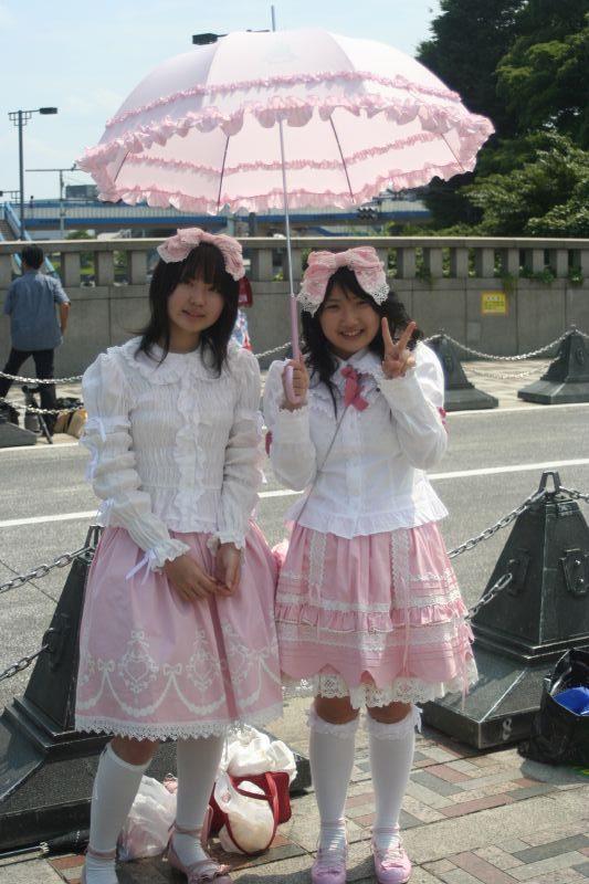 zwei japanische Frauen mit Sonnenschirm im rosa Lolita-Look posieren für ein Foto