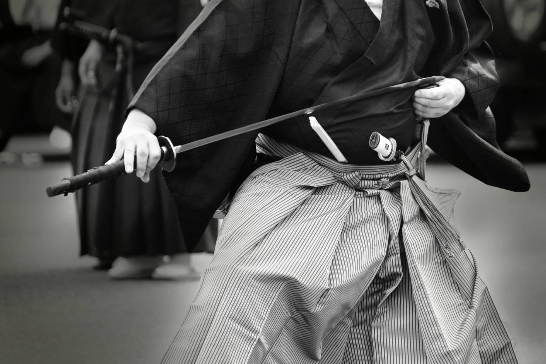 Ein in japanischem Gewand gekleideter Mann zieht ein Katana aus der Scheide