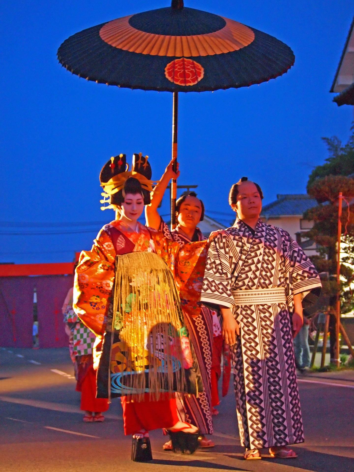 Oiran auf der Straße mit einem Sonnenschirmträger