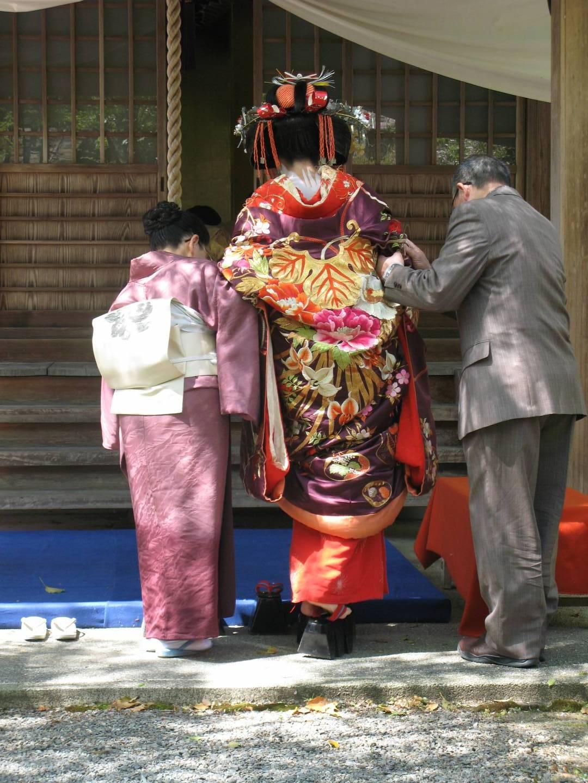 Orian von hinten mit Herr im Anzug und Frau in Komono gekleidet