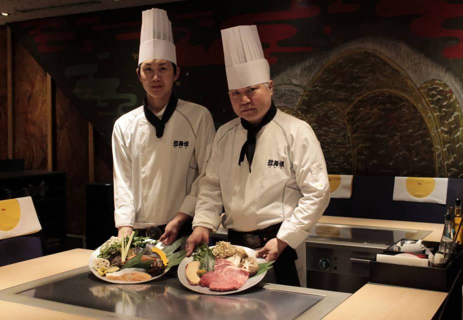 Zwei Köche posieren vor einem teppanyaki Grill mit Speisen