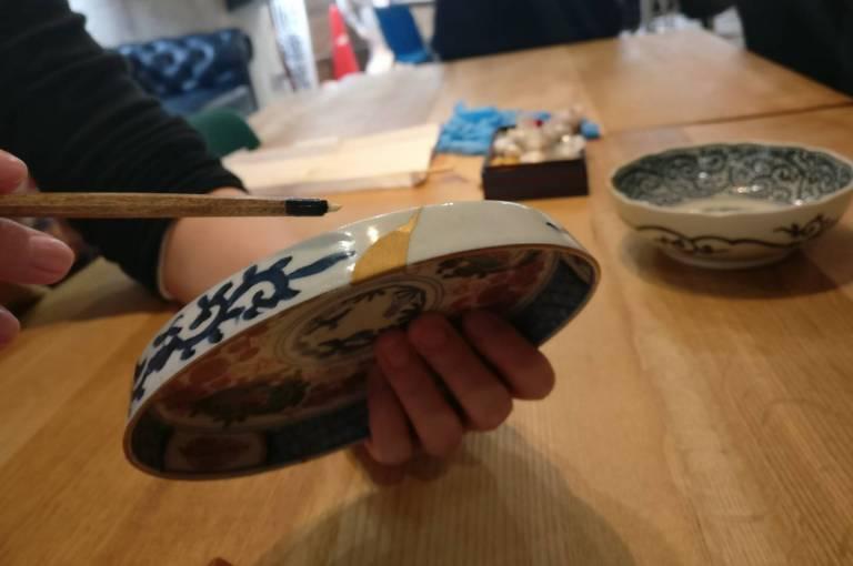 Ein gesprungener Teller wird mit Goldlack repariert.