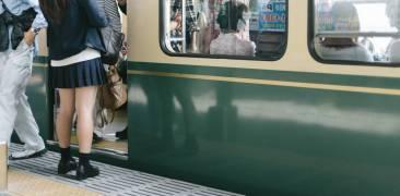 japanischer Zug mit einsteigenden Passagaieren am Bahnhof