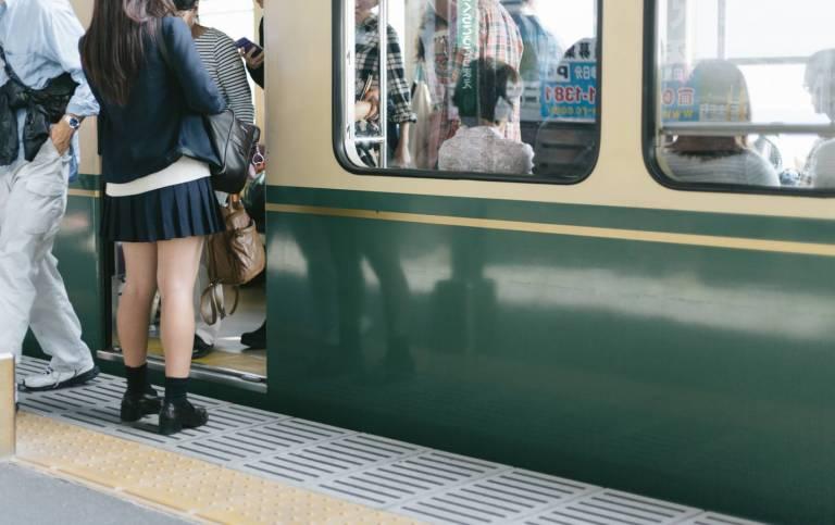 japanischer Zug mit einsteigenden Passagieren am Bahnhof