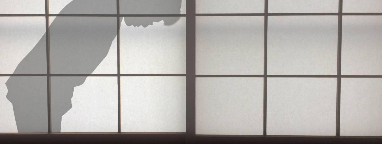 Shilouette eines sich verbeugenden Manns hinter einem Papierfenster