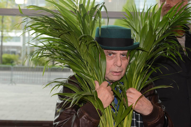 Sylvester McCoy versteckt sich hinter einer Pflanze