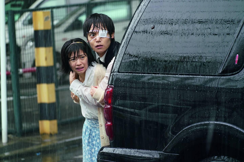 Filmausschnitt Tokyo Ghoul: Mann und Mädchen kauern hinter Auto im Regen