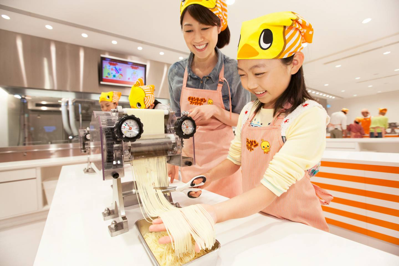 Frau und Mädchen machen Nudeln für Chicken Ramen im Cupnoodles Museum in Yoykohama