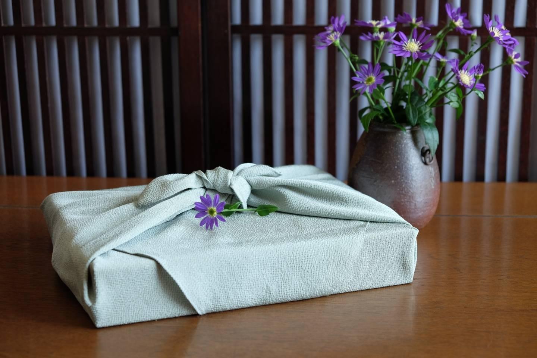 in ein Stofftuch gewickeltes Geschenk und Blumenvase im Hintergrund