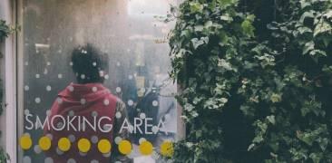 Mann lehnt mit dem Rücken gegen die Wand eines Raucherbereichs in Sibuya