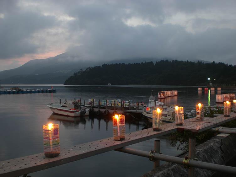 Beim Torii Yaki Matsuri schwimmen Tausende von leuchtenden Laternen auf dem See Ashi.