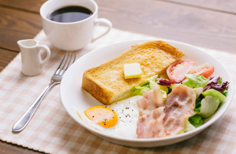 Westliches Frühstück mit Toast, Bacon, Spiegelei und Kaffee