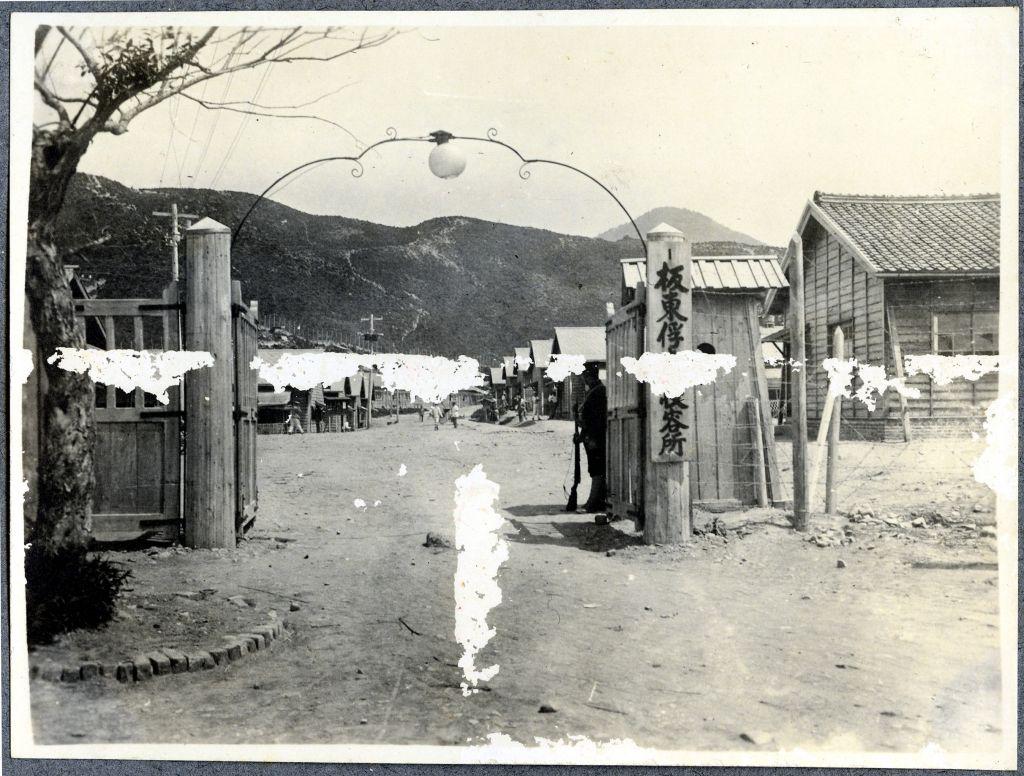 Blick auf das Kriegsgefangenenlager durch das Eingangstor.