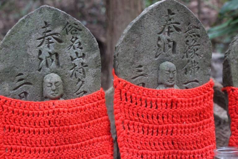 Alte Statuen in rotem Strickkostüm.
