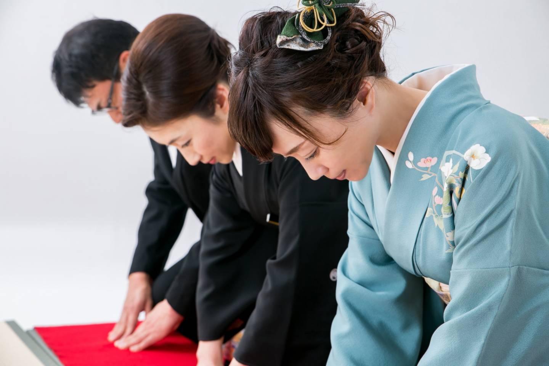 drei JapanerInnen verbeugen sich