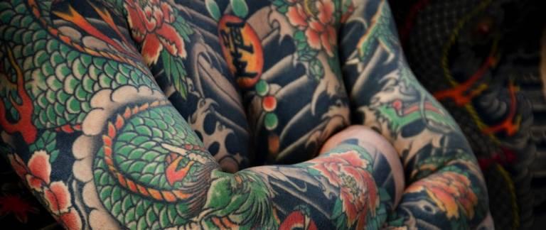 Traditonelles Ganzkörper-Tattoo mit Drachen- und Blumenmotiven.