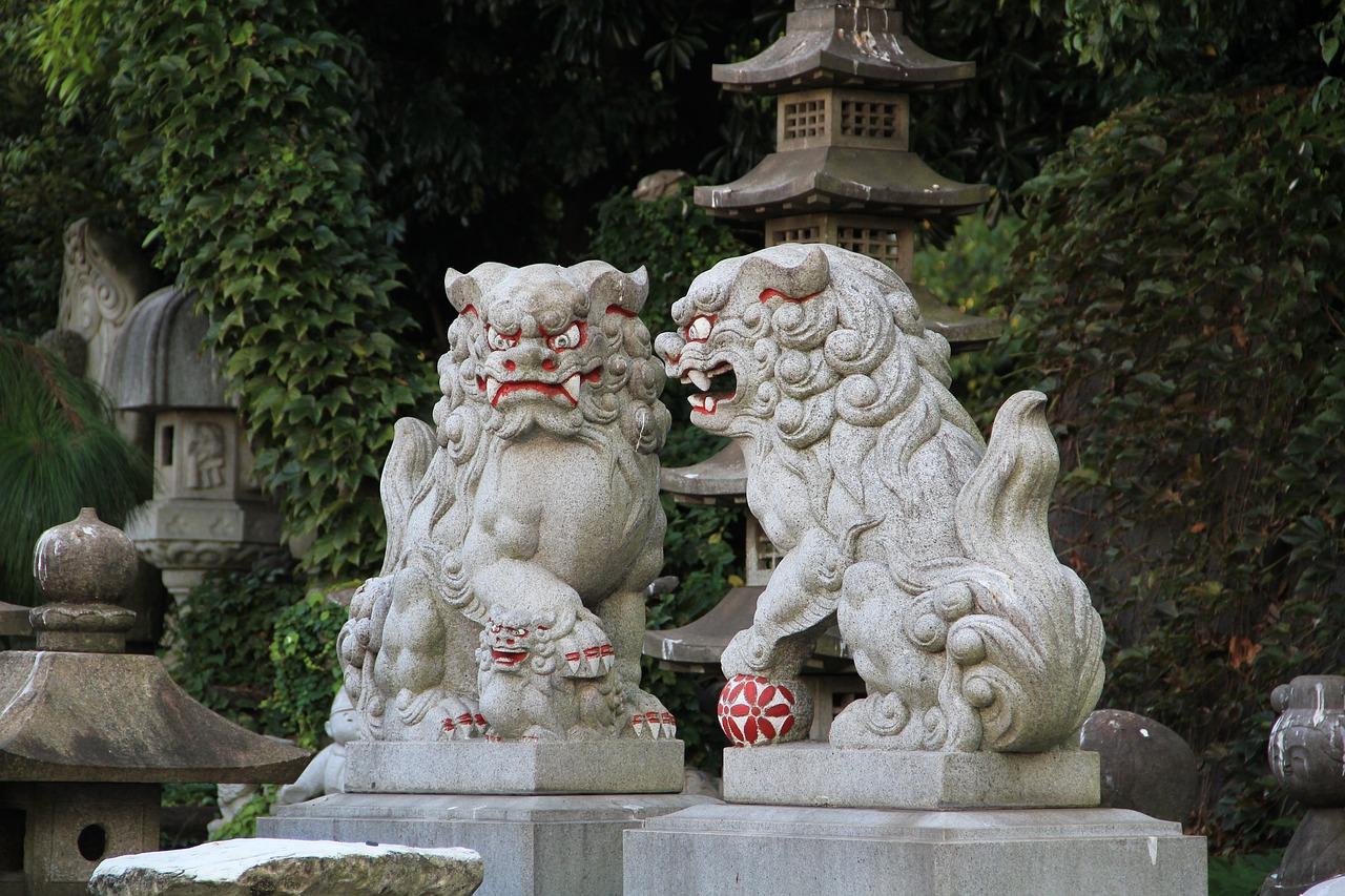 zwei steinerne Komainu vor Bäumen