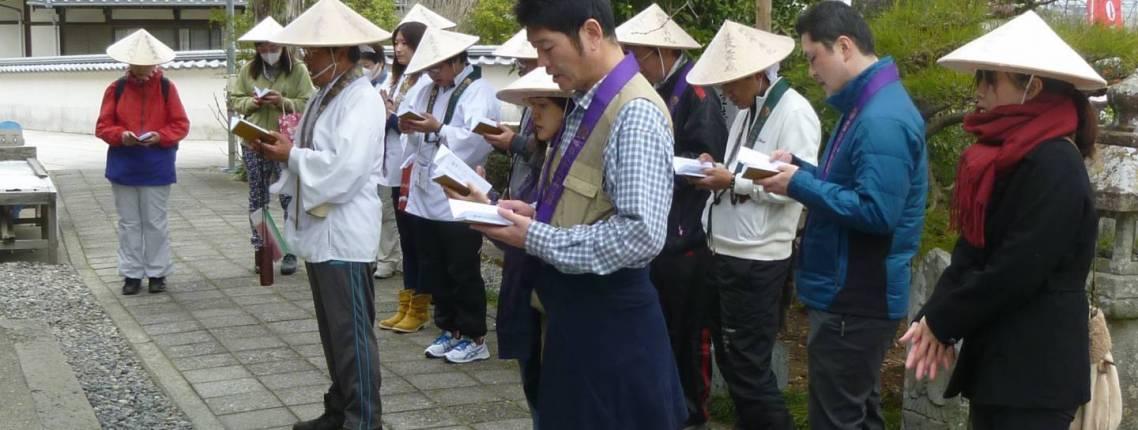 Yoshida (mitte) rezitiert Sutren vor einem Tempel.
