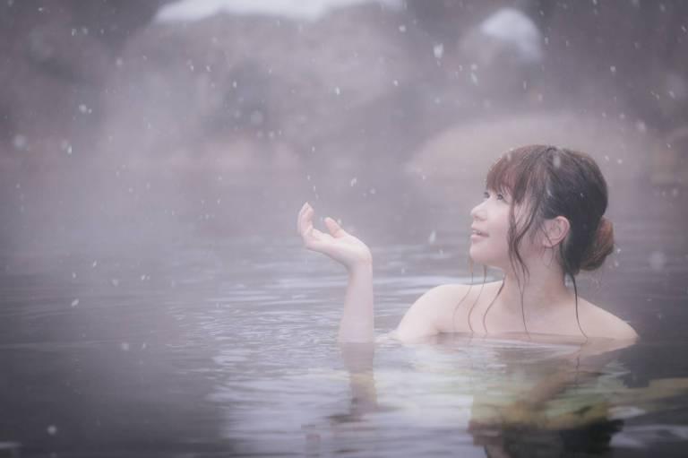 Bei Schnee im Onsen entspannende Frau
