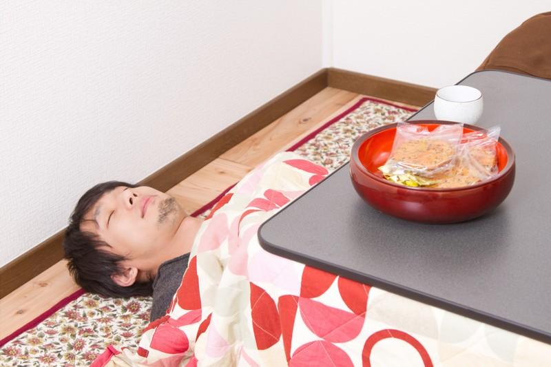 Schlafender Mann unter einem kotatsu (beheizter Tisch)