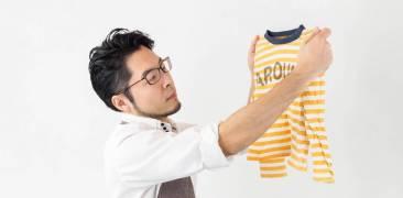 mann betrachtet kinderpullover