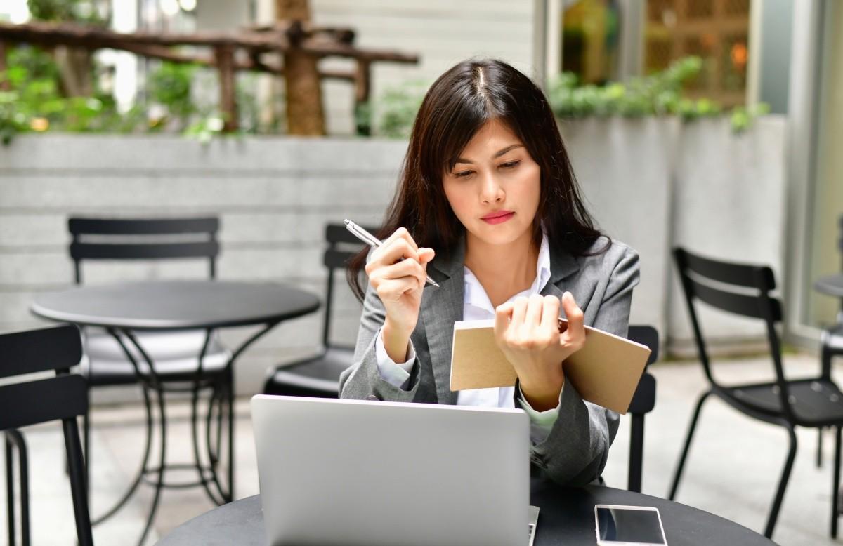 Frau mit Notizbuch, vor ihr ein Laptop auf einem Tisch