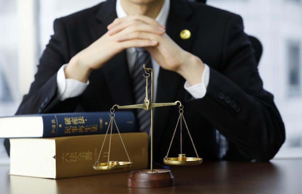 Waage und Gesetzesbücher auf einem Tisch angerichtet, dahinter der Torso eines sitzenden Mannes im Anzug
