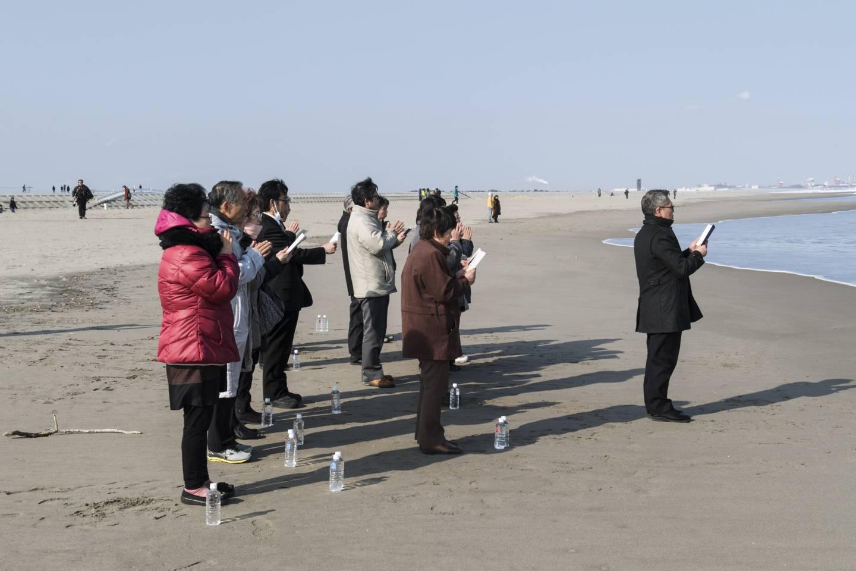 für die opfer der katastrophe fukushima betende personen am strand