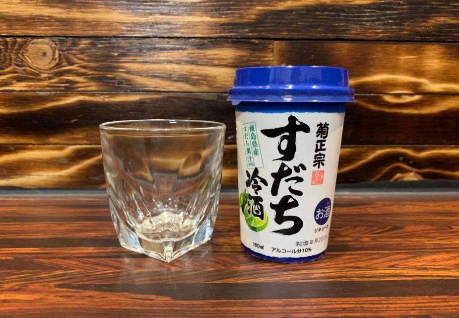 ein leeres Glas und ein Bescher Sudachi-Shu auf einem Tresen