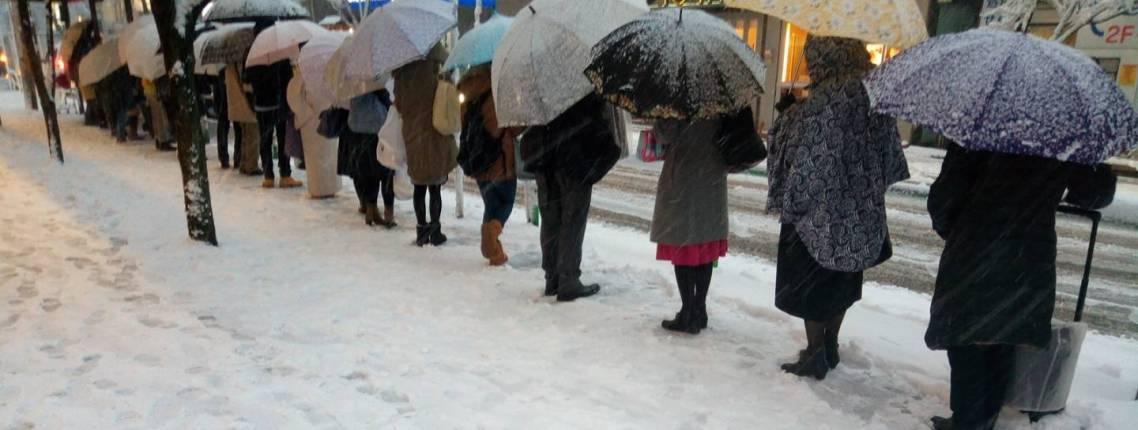 Japaner, die im Schnee Schlange stehen.