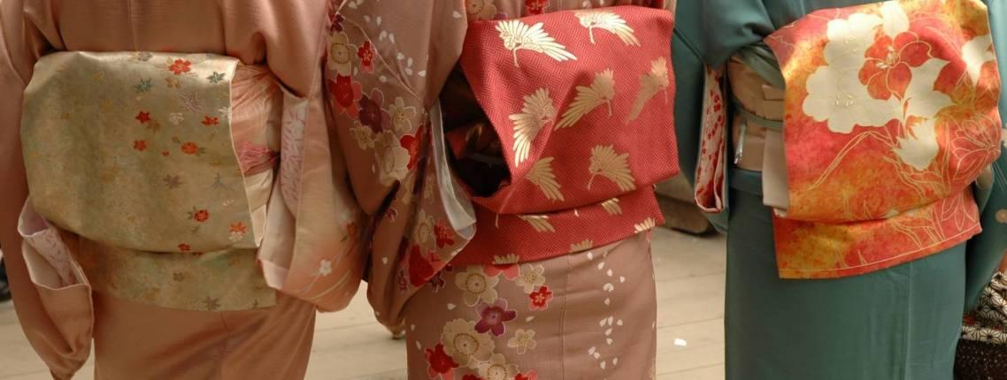 Nahaufnahme von drei Obi an Frauen im Kimono.