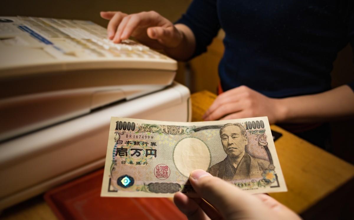hand hält yen-schein zur kasse