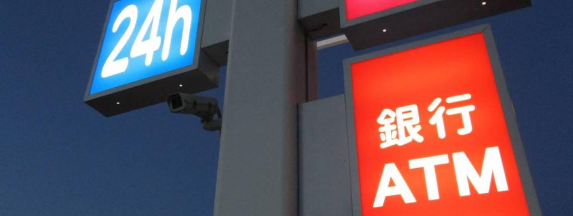 Schild über einem Kombini zeigt u.a. eine Öffnungszeit von 24 Stunden an.