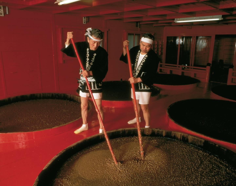 2 Männer rühren in einem Bottich mit Sojasauce, um diese zu fermentieren.