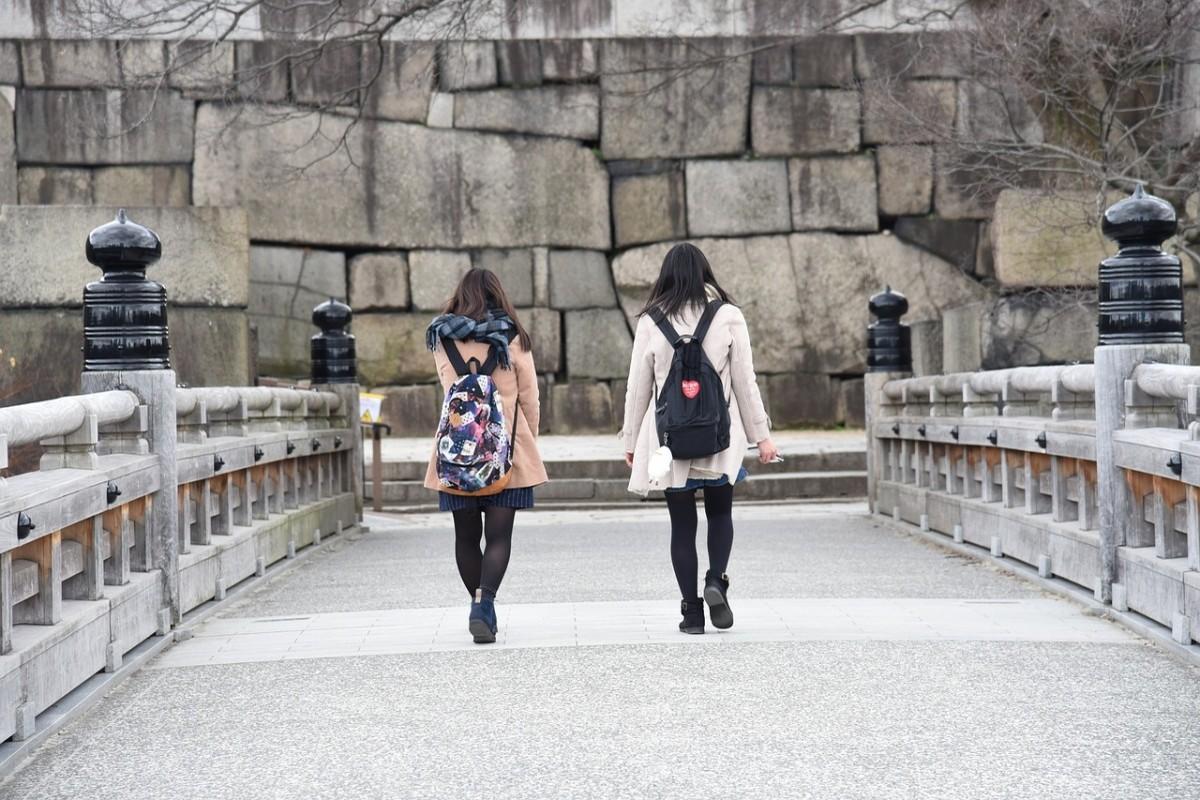 Zwei Frauen von hinten gehen auf eine japanische Burg zu