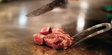 Nahhaufnahme von Fleisch auf einer heißen Grillplatte mit Messer