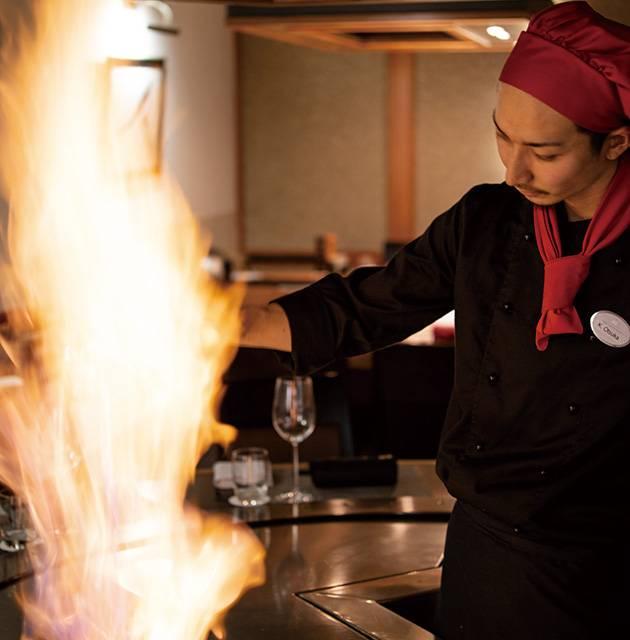 flamme über einem teppanyaki Grill mit koch