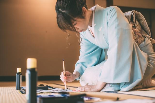Frau im Kimono beim Kalligrafieren