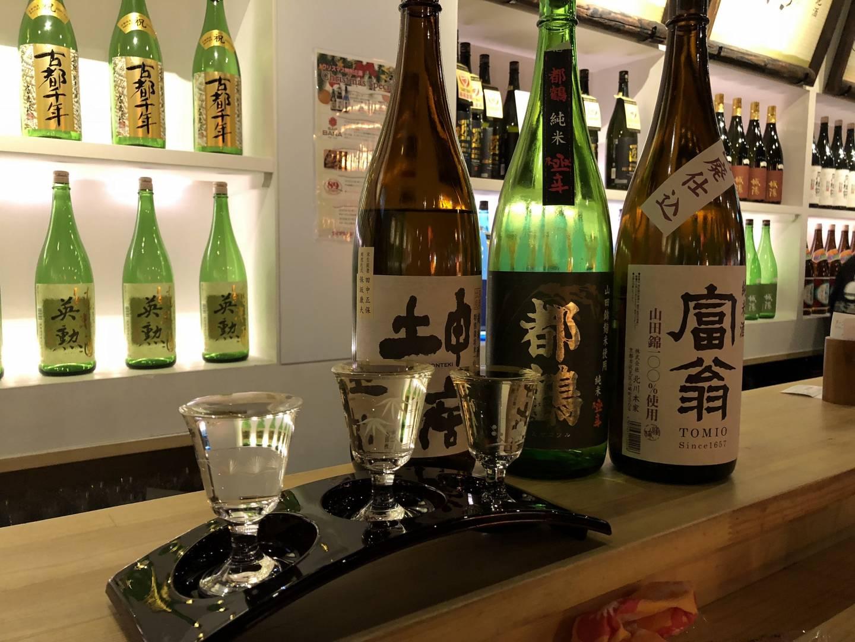 Sake in Flaschen und Gläsern auf einer Theke