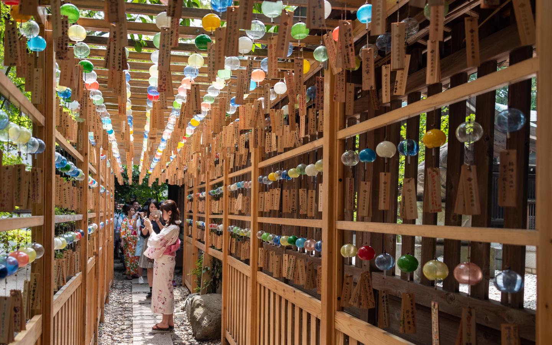 Windspiele in einer Passage aufgehängt, durch die junge Frauen im Yukata spazieren