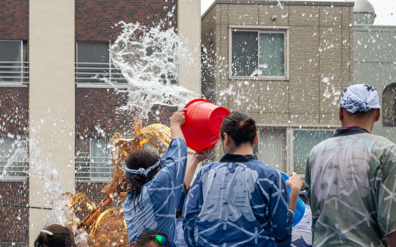 Menschen schütten Wasser auf eine Schreinparade bei einem Fest